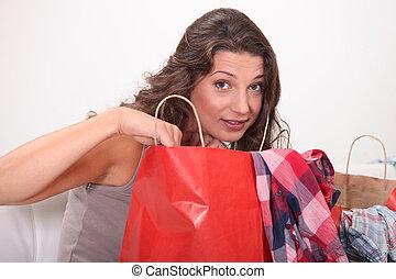 Young woman at home examining shopping bags