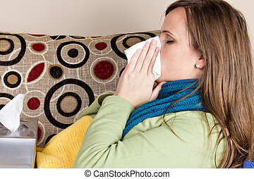 Young woman at home having flu, blowing her nose