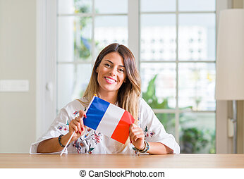 Young woman at home holding flag of France with a happy face standing and smiling with a confident smile showing teeth