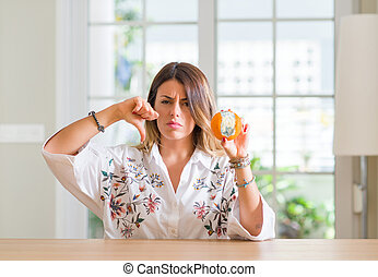 Young woman at home holding rotten orange with angry face, negative sign showing dislike with thumbs down, rejection concept