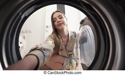 Young woman at home picks up dresses from drying machine. -...