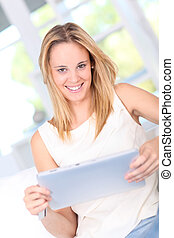 Young woman at home using electronic tablet