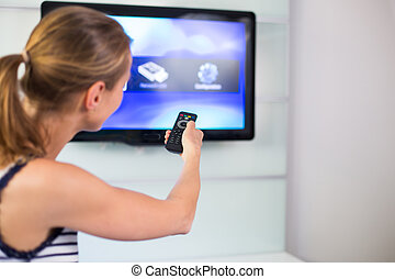 Young woman at home watching TV