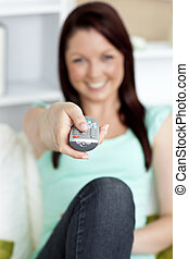 young woman at home with a remote