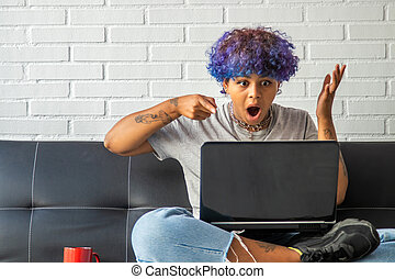 young woman at home with laptop sitting on the living room sofa
