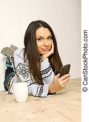 Young woman at home with the phone
