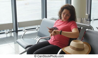 Young woman at international airport looking at smartphone and waiting her flight