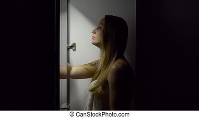 Young woman at night opens a wardrobe and choose the dress...