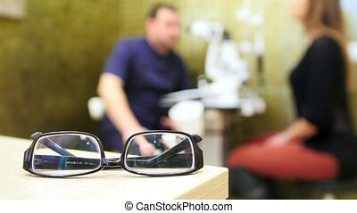 Young woman at ophthalmology doctor - checking Eyesight in...