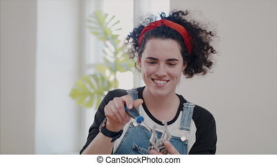 Young woman at repair cafe repairing household electrical devices.