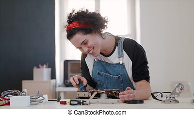 Young woman at repair cafe repairing household electrical ...