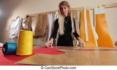 Young woman at sewing factory. A woman takes a template from the wall.