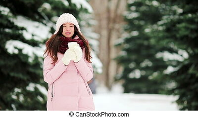 Young woman at snow weather outdoors with coffee to go on beautiful winter day