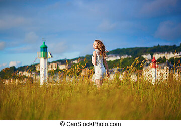 Young woman at sunset on meadow near lighthouse