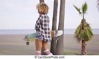 Young woman at the beach with her skateboard - Young woman...