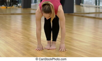 Young woman at the gym makes a body workout before training.