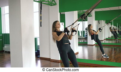 Young woman at the gym working on on trx and training arms with fitness straps in the gym