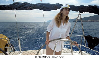 Young woman at the helm of a yacht in the open sea
