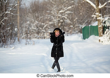 Young woman at winter in the snowy forest or park.