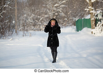 Young woman at winter in the snowy Park.