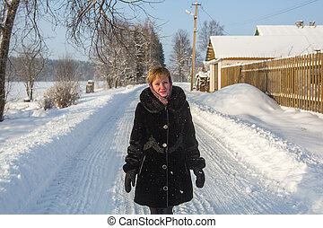 Young woman at winter in the snowy village.