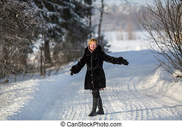 Young woman at winter on the snowy road in russian village.