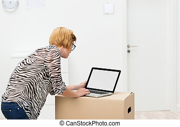 Young woman at work in her new house