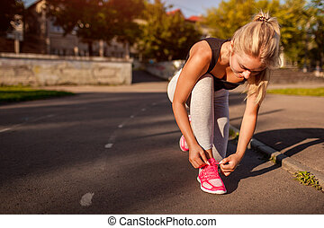 Young woman athlete tying sneakers on running track on sportsground in summer. Preparation for training