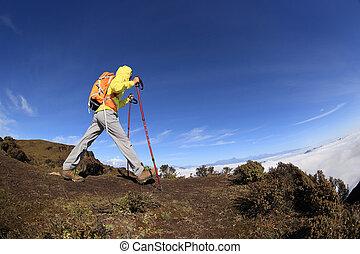 young woman backpacker climbing on mountain peak