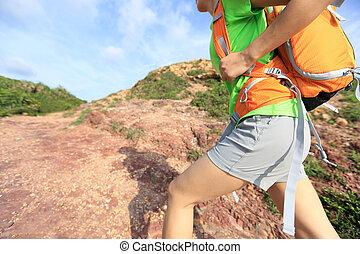 young woman backpacker climbing on mountain trail