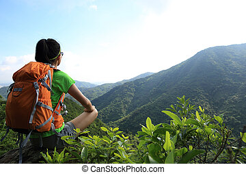 young woman backpacker  enjoy the view on mountain peak