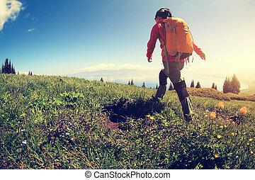 young woman backpacker hiking on beautiful mountain peak