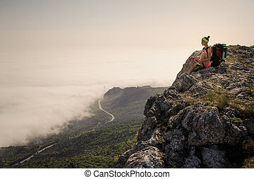 young woman backpacker hiking on beautiful mountain peak trail.