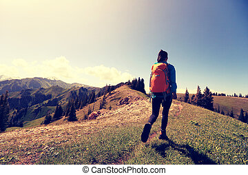 young woman backpacker hiking on forest mountain peak