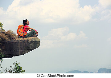 young woman backpacker hiking on mountain peak cliff