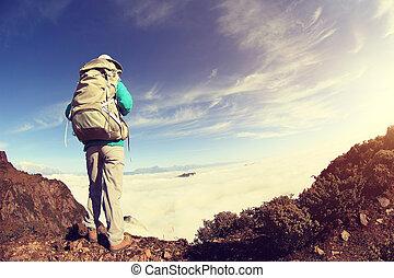 young woman backpacker hiking on mountain peak