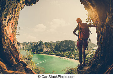 young woman backpacker hiking on seaside mountain cliff