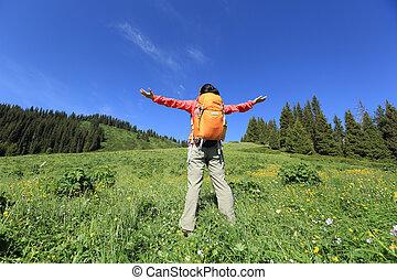 young woman backpacker hiking on sunrise mountain peak