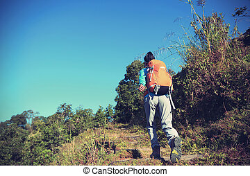 young woman backpacker trekking at mountain peak
