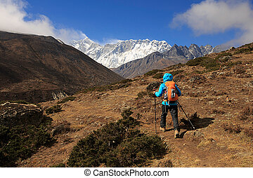 young woman backpacker trekking on himalaya mountains, drying socks with sunshine on the backpack