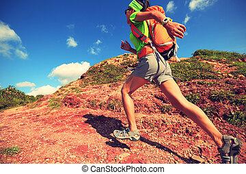 young woman backpacker walking on seaside mountain trail