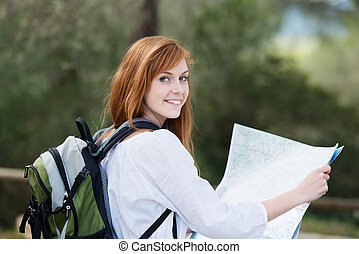 Young woman backpacking in nature with a rucksack on her back and a topographical map in her hands