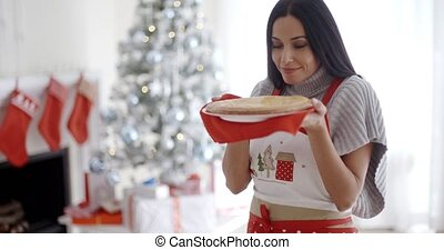 Young woman baking Christmas treats standing in her festive...
