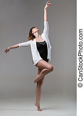 young woman ballerina ballet dancer dancing on gray background