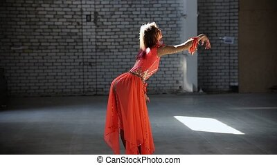 Young woman ballerina in orange dress making a gracefully...