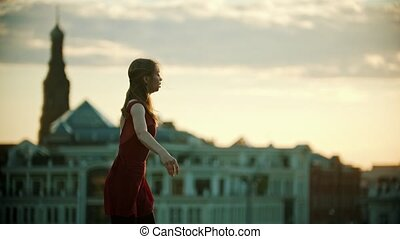 Young woman ballerina in red dress dancing on the roof - runs up and jump performing a split - bright sunset