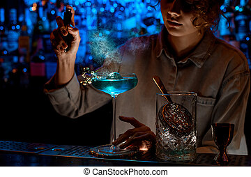Young woman bartender gently sprinkles on glass with blue cocktail