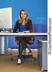 Young woman behind desk - Young pretty woman sitting behind...