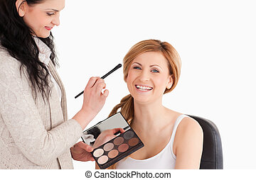 Young woman being made up by a make