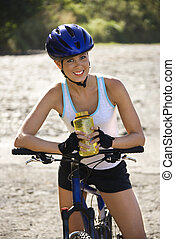 Caucasian mid-adult woman wearing bicycle helmet, sitting on bycycle, holding water bottle, looking at viewer, smiling.